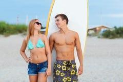 Couples de sourire dans des lunettes de soleil avec des ressacs sur la plage Images libres de droits