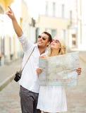 Couples de sourire dans des lunettes de soleil avec la carte dans la ville Images stock