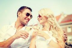 Couples de sourire dans des lunettes de soleil buvant du vin en café Image stock