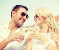 Couples de sourire dans des lunettes de soleil buvant du vin en café Images stock