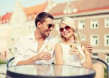 Couples de sourire dans des lunettes de soleil buvant du vin en café Photographie stock