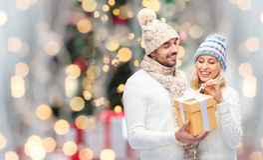 Couples de sourire dans des vêtements d'hiver avec le boîte-cadeau Image stock