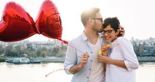 Couples de sourire dans l'amour avec des ballons sur le coucher du soleil Photos libres de droits