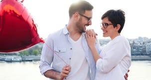 Couples de sourire dans l'amour avec des ballons sur le coucher du soleil image libre de droits