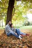 Couples de sourire dans l'amour en automne en parc Image stock