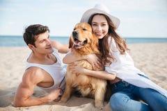 Couples de sourire dans l'amour se reposant sur la plage avec le chien Photos stock