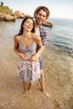 Couples de sourire dans l'amour se tenant à la plage et à étreindre Photo stock