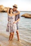 Couples de sourire dans l'amour se tenant à la plage et à étreindre Image libre de droits