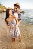 Couples de sourire dans l'amour se tenant à la plage et à étreindre Photos libres de droits
