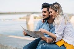 Couples de sourire dans l'amour voyageant avec une carte dehors Photographie stock