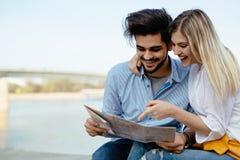Couples de sourire dans l'amour voyageant avec une carte dehors Image stock