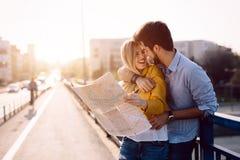 Couples de sourire dans l'amour voyageant avec une carte dehors Images stock