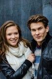 Couples de sourire dans l'habillement d'hiver regardant loin Photos stock