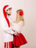 Couples de sourire dans le chapeau du père noël Noël Image stock