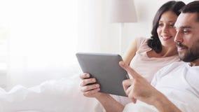 Couples de sourire dans le lit avec l'ordinateur de PC de comprimé banque de vidéos