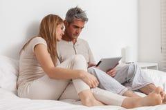 Couples de sourire dans le lit utilisant l'ipad Image stock