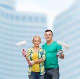 Couples de sourire dans les gants avec des rouleaux de peinture Photos libres de droits