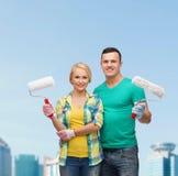 Couples de sourire dans les gants avec des rouleaux de peinture Images stock