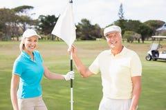 Couples de sourire de golfeur tenant le drapeau blanc Photographie stock