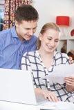Couples de sourire discutant des finances domestiques à la maison images libres de droits