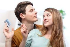 Couples de sourire drôles utilisant la carte de crédit à la boutique d'Internet en ligne Photographie stock libre de droits