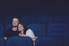 Couples de sourire embrassant et observant le film drôle dans le cinéma Photo stock