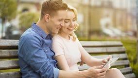 Couples de sourire en photos de visionnement d'amour des vacances sur le comprimé, utilisant l'APP mobile Photographie stock
