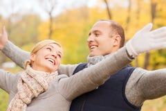 Couples de sourire en stationnement d'automne Photographie stock libre de droits