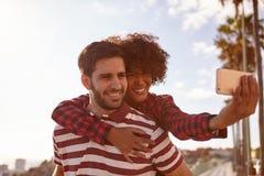 Couples de sourire espiègles prenant des selfies d'amusement Image stock
