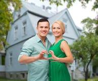 Couples de sourire et représentation du geste de forme de coeur Photographie stock