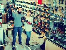 Couples de sourire examinant de diverses espadrilles dans la boutique Photographie stock libre de droits