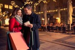 Couples de sourire examinant la liste d'achats pour assurer Noël Image libre de droits