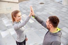 Couples de sourire faisant la haute cinq sur la rue de ville Photographie stock