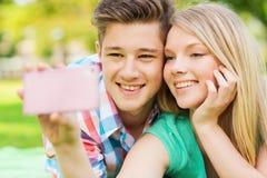 Couples de sourire faisant le selfie en parc Image stock