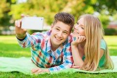 Couples de sourire faisant le selfie en parc Images libres de droits