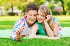 Couples de sourire faisant le selfie en parc Photographie stock