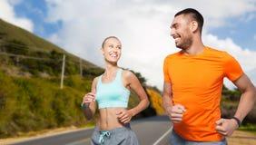 Couples de sourire fonctionnant au-dessus des collines de Big Sur photographie stock