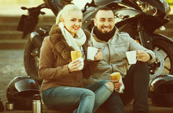 Couples de sourire gais ayant le pique-nique avec du café Photos stock