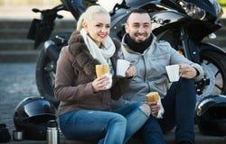 Couples de sourire gais ayant le pique-nique avec du café Photographie stock libre de droits