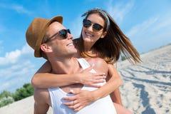 Couples de sourire gais se reposant sur la plage Photos libres de droits