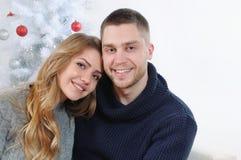 Couples de sourire heureux à l'arbre de Noël Photo stock