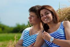 Couples de sourire heureux étreignant sur la meule de foin Photos stock