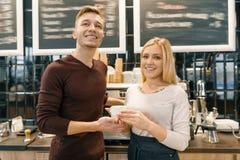 Couples de sourire heureux au compteur, aux travailleurs ou aux propriétaires de café avec une tasse de café frais d'art regardan photo stock
