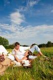 Couples de sourire heureux ayant le pique-nique Photographie stock libre de droits
