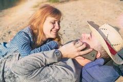 Couples de sourire heureux détendant sur le sable Homme parlant du p Photos libres de droits