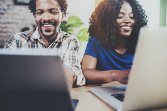 Couples de sourire heureux d'afro-américain fonctionnant ensemble à la maison Jeune homme de couleur et son amie à l'aide de l'or Photos libres de droits