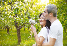 Couples de sourire heureux dans l'amour dans le jardin bloomy Image stock