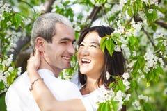Couples de sourire heureux dans l'amour dans le jardin bloomy Photos libres de droits