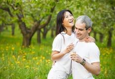 Couples de sourire heureux dans l'amour dans le jardin bloomy Photo stock