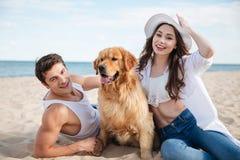Couples de sourire heureux dans l'amour se reposant sur la plage avec le chien Photos libres de droits